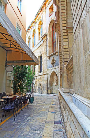 An alley with cafe and the Sagredo Fountain, Built by Giovanni Sagredo between 1602-1604, which is in the northwest corner of today's Loggia building in Heraklion, Crete, Greece.