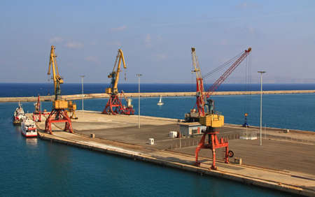 Harbor with industrial loading dock for ships in Heraklion, Crete, Greece with blue sky copy space, tug boats and a sailboat.