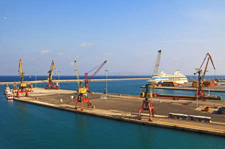Harbor with industrial loading dock for ships in Heraklion, Crete, Greece with a cruise ship docked nearby, tug boats and blue sky copy space. 版權商用圖片