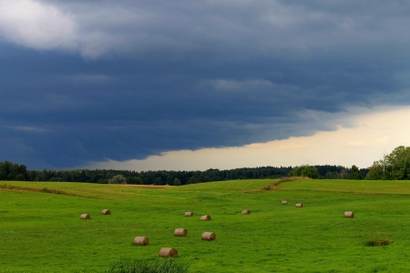 hayroll: thunderstorm clouds over farmfield Stock Photo