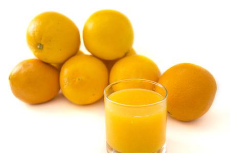 Fresh oranges and juice isolated over white background
