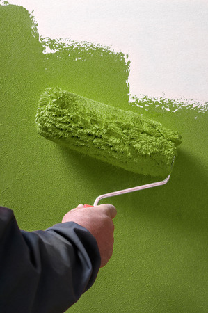painter: Smooth concrete wall hand painting with paint roller - painter