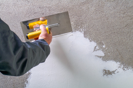 Construction worker plastering and smoothing concrete wall with white cement by a steel trowel