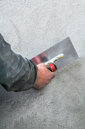 smoothing: Construction worker smoothing - plastering concrete wall by a steel trowel - spatula aligns