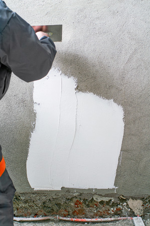 smoothing: Construction worker plastering and smoothing concrete wall with white cement by a steel trowel Stock Photo