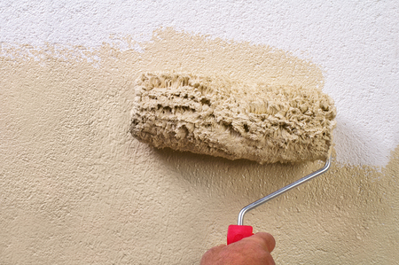 Facades wall painting with paint roller - hand applying