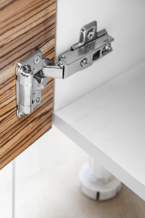 Closeup of furniture cabinet modern clip hinge with amortization. Standard-Bild