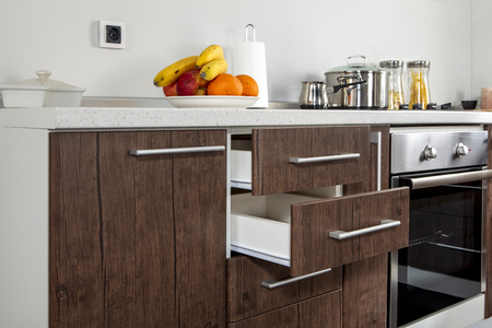 Part of modern kitchen with electric stove oven, drawers, handle and fruits 写真素材
