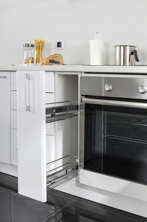 Part of modern kitchen with electric stove oven details, drawers, sink 写真素材