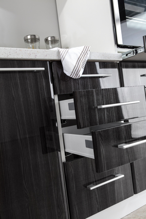 Part of modern kitchen with electric stove oven details, drawers, sink Standard-Bild