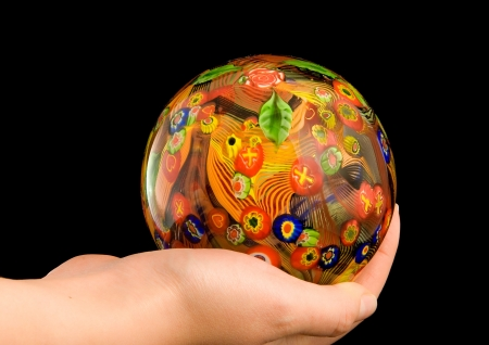 Glass ball made on Murano Island (near Venice) in a hand of a woman photo
