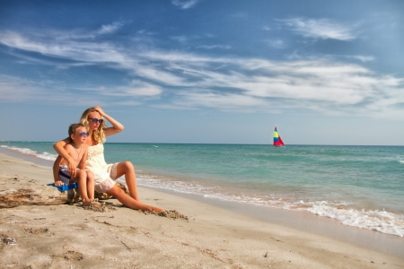 blonde mother and son sitting on the beach and watch the sailboat photo