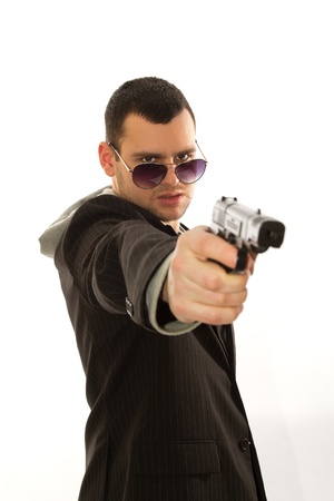 a young man wearing a jacket with a gun in his hand Stock Photo