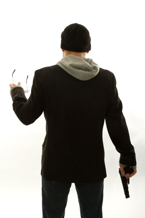 murdering: a young man wearing a jacket with a gun in his hand Stock Photo