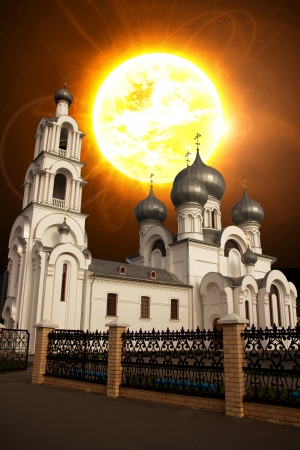 the sun shines over the Catholic church. possible end of the world. Armageddon photo