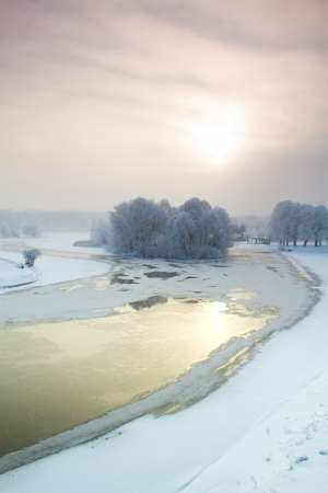 Winter sunrise over the river. trees under the snow photo
