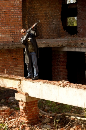 a man with a gun in his hand and a cigarette in the ruins of the house