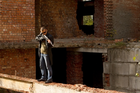 a man with a gun in his hand and a cigarette in the ruins of the house photo