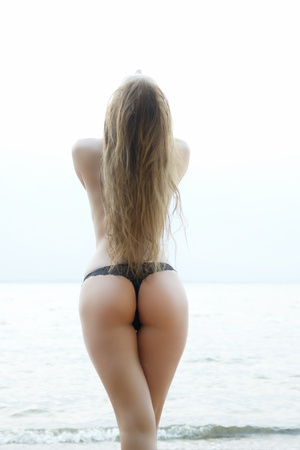 sexy girl with a figure standing at the sea showing her ass photo