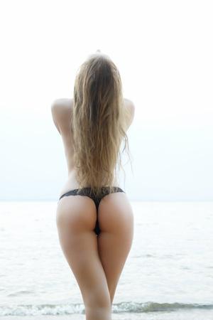 sexy Mädchen mit einer Figur, die am Meer zeigt ihren Arsch