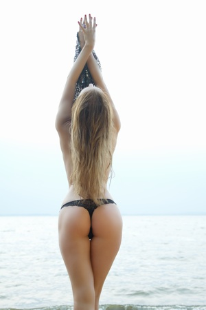 ass fun: sexy girl with a figure standing at the sea showing her ass Stock Photo