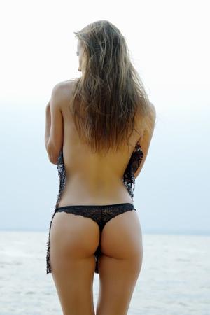 culo: chica sexy con una figura de pie en el mar mostrando su culo