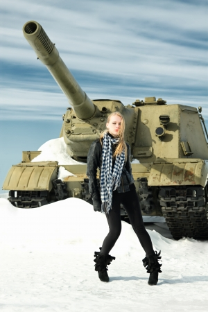 brutal girl stands amid battle tank photo