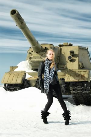 cannon gun: brutal girl stands amid battle tank Stock Photo