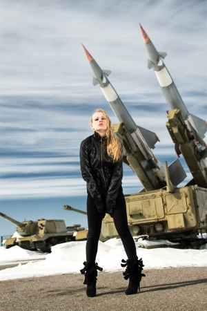 brutal girl standing on a background of military ballistic missiles photo