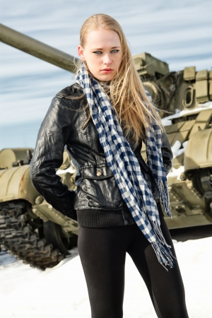 weaponry: brutal girl stands amid battle tank Stock Photo
