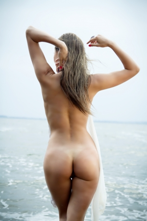sunbathe: sexy girl with a figure standing at the sea showing her ass Stock Photo