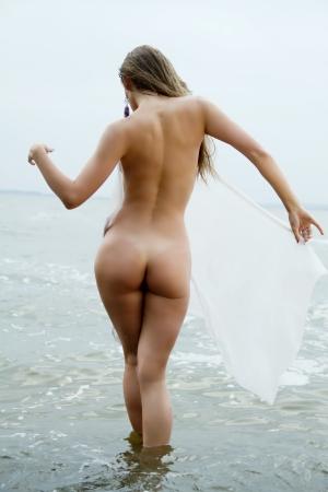 ni�as en bikini: chica sexy con una figura de pie en el mar que muestra su culo Foto de archivo