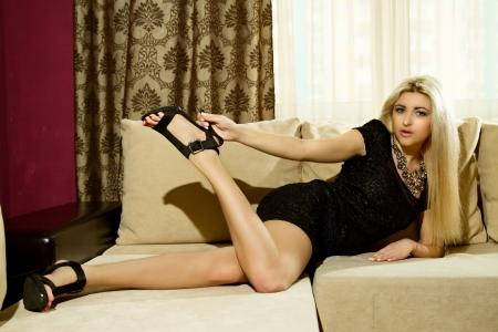 sexy meisje in een zwarte jurk liggend op de bank