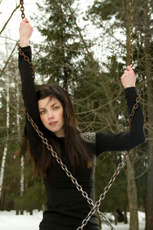 girl in a dress standing in the woods with chains on his hands photo