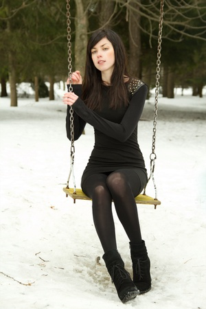 girl sitting on a swing in the winter in a black dress photo
