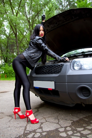 legs open: girl in the forest opened the cars hood Stock Photo