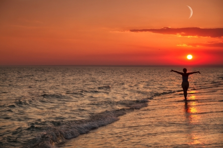 Mädchen zu Fuß am Strand bewundert den Sonnenuntergang am Meer