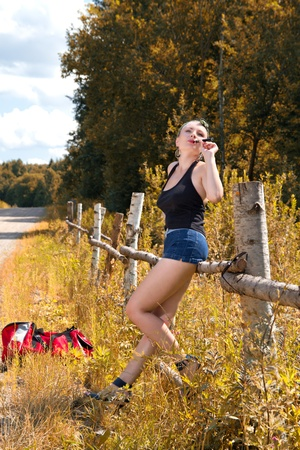 sexy girl in the style of pin-up with e-sigoretoy is on the road in the woods