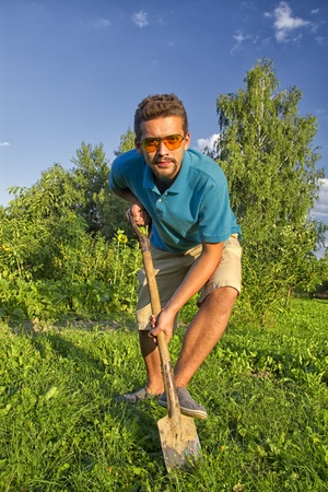 young man with a shovel digging a vegetable garden photo