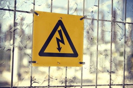 dramatics: Electricity sign hanging on the fence Stock Photo