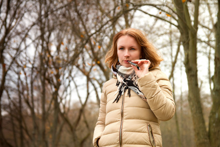 girl with the electronic cigarette in the park autumn Stock Photo
