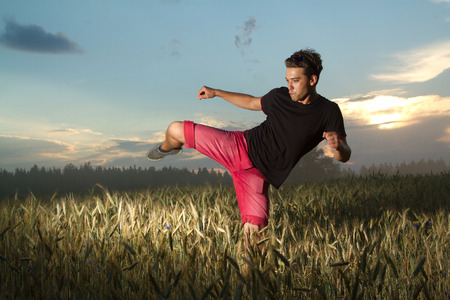 man goes in for sports. at sunset man trains in martial arts  photo