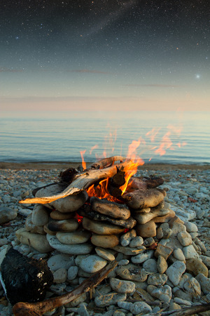Inviting campfire on the beach during the summer.  photo