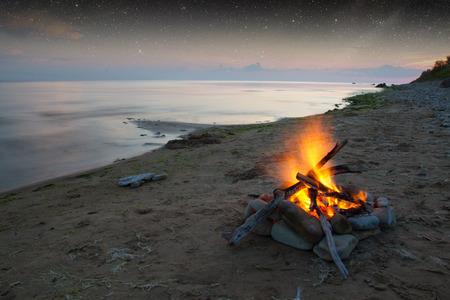 Uitnodigende kampvuur op het strand tijdens de zomer. Stockfoto