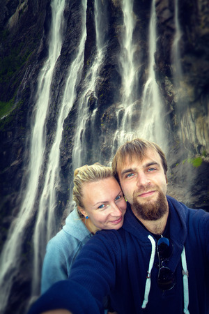 man waterfalls: waterfalls northern Norwegian fjords. Honeymoon couple relaxing in Europe, a man and a woman.