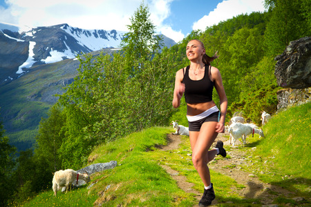 girl on a morning jog in the summer outdoors. goats in the mountains. in the picturesque fjords of Norway