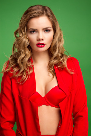 Sexy girl in red on a green background. in a jacket and skirt bra. photo