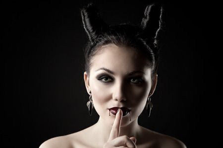 tempter: The girl in the image of the demon-tempter and hair in the form of horns. Photo taken in the studio on a background.