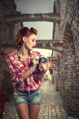 despite: pin-up with a camera. Sexy redhead woman tourist on the narrow medieval streets of Tallinn despite the weather at the camera photographs the architecture. vintage retro