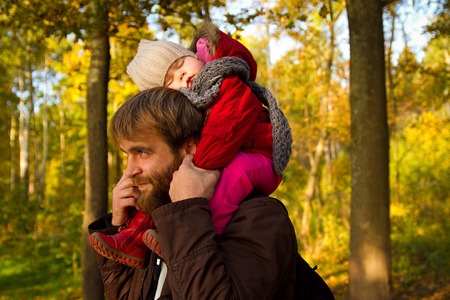 Dad and daughter. daughter fell asleep on his neck with his father in autumn park photo